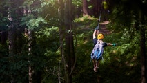 rear view of woman in the forest with her backpacker enjoying adventure on tyrolean traverse.