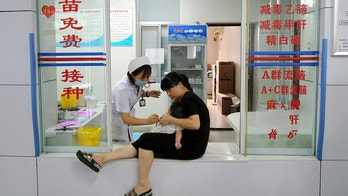 In this July 24, 2018, photo, a woman holds an infant as a nurse administers a vaccination at a Chinese Center for Disease Control and Prevention (CDC) station in Jiujiang in southern China's Jiangxi province. Chinese state media report a total of 15 people have been detained so far in a growing scandal over the faking of records by a rabies vaccine maker, including the CEO of Changchun Changsheng Life Sciences Ltd. (Chinatopix via AP)
