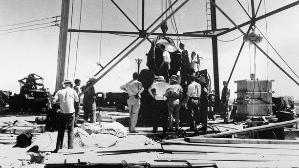 FILE - In this July 6, 1945, file photo, scientists and workmen rig the world's first atomic bomb to raise it up onto a 100 foot tower at the Trinity bomb test site near Alamagordo, N.M. The National Cancer Institute said its long-anticipated study into the cancer risks of New Mexico residents living near the site of the world's first atomic bomb test likely will be published in 2019. Institute spokesman Michael Levin told The Associated Press that researchers are examining data on diet and radiation exposure and expect to finish the study by early next year. (AP Photo/File)