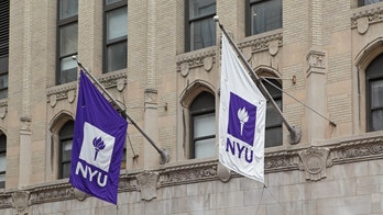 New York, NY, USA - June 3, 2015: Purple and white NYU flags hang from a New York University building on West 4th Street in Manhattan. In 1965, graphic artist Tom Geismar designed the torch logo now used on all NYU flags.
