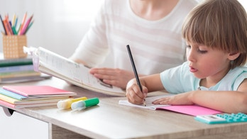 Boy focusing on homework while sitting with mother at desk with notebook and colored pens
