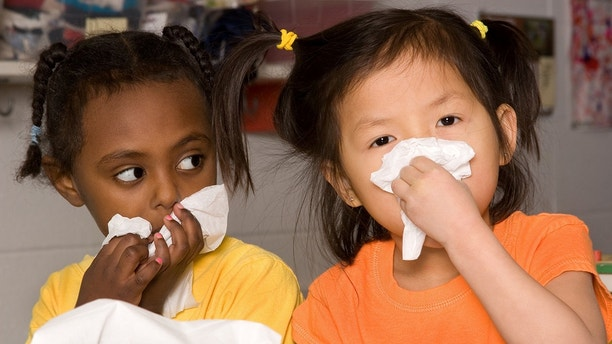 Chinese little girl wipes her nose with tissue as friend watches (shallow dof)