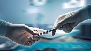 healthcare and medical concept , Close-up of surgeons hands holding surgical scissors and passing surgical equipment , motion blur background.