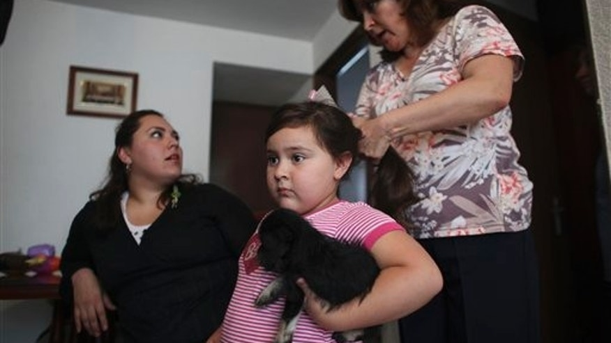 In this photo taken on Tuesday July 19, 2011, Elizabeth Sucilla combs the hair of her four-year-old granddaughter Anghella Torres before going out for a walk, at their home in Mexico City. Anghella weighs 66 pounds (30 kilos) - twice what she should. With the help of her grandmother, Anghella is following a modest diet and exercise program established for her by a nurse at a local public hospital earlier this year. Anghella's mother, Livni Schroeder, 25, is pictured at left. (AP Photo/Alexandre Meneghini)