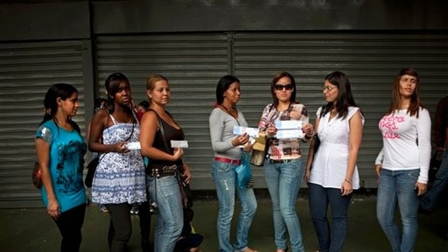 Women affected by breast implants made by the defunct French brand Poly Implant Prothese, PIP, show their breast implants certificate to journalists outside the civil court in Caracas, Venezuela, Friday, Jan 06, 2012. According to lawyer Emilia De Leon, around 400 women affected by breast implants made by PIP, filed Friday a request for an injunction against the implants' distributors in Venezuela, demanding that they cover their medical expenses. (AP Photo/Ariana Cubillos)