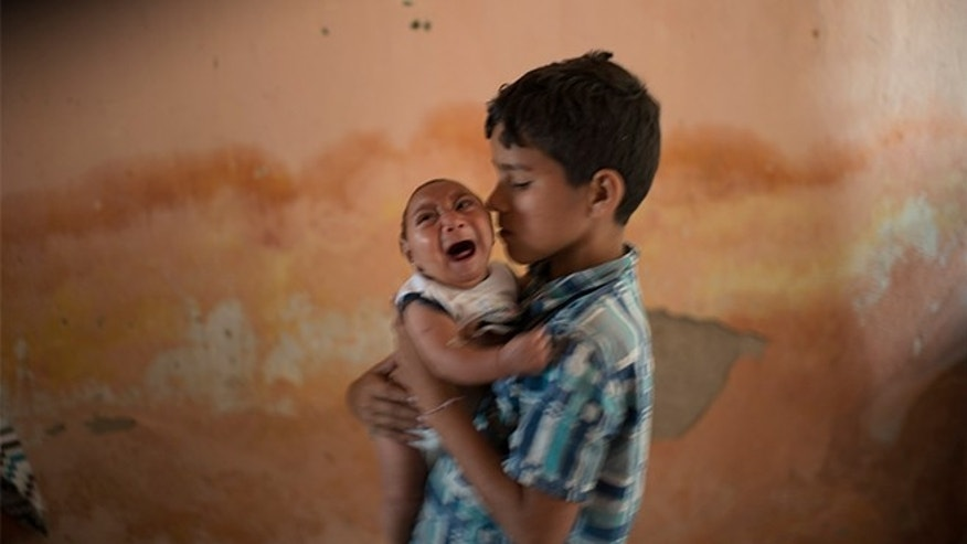 FILE - In this Dec. 23, 2015, file photo, 10-year-old Elison nurses his 2-month-old brother Jose Wesley, who was born with microcephaly, at their house in Poco Fundo, Pernambuco state, Brazil. The U.S. Centers for Disease Control and Prevention said Wednesday, Jan. 13, 2016, that it has found the strongest evidence so far of a possible link between a mosquito-borne virus and a surge of birth defects in Brazil.