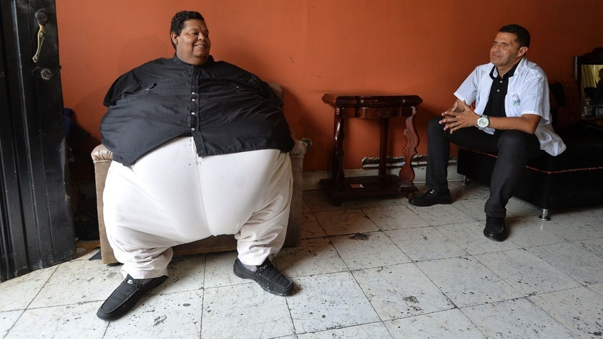 "Oscar Vasquez Morales (L), 44, speaks with Salvador Palacio, director of the ""Gorditos de Corazon"" (Chubby at Heart) foundation, on March 19, 2016, in Palmira, Colombia. Vasquez, who weighs about 400 kilos and is considered the fattest man in the country, is expected to lose 300 kilos in the next 3 or 4 years due to a medical treatment.  AFP PHOTO / LUIS ROBAYO / AFP / LUIS ROBAYO        (Photo credit should read LUIS ROBAYO/AFP/Getty Images)"