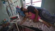 In this Aug. 11, 2016 photo, 3-year-old Ashely Pacheco rests with her father Maykol Pacheco in her hospital bed at the University Hospital in Caracas, Venezuela. Two weeks after 3-year-old Ashley scraped her knee, she was screaming in a hospital, fighting for her life as her family scoured Caracas for scarce antibiotics. Venezuela is running short on 85 percent of basic medicines. As the health care system collapses, the tiniest slips, like a little girlâs tumble while chasing her brother, are turning into life-or-death crises. (AP Photo/Ariana Cubillos)
