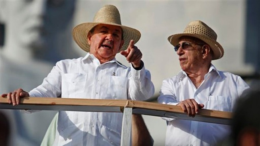 In this photo taken May 1, 2010, Cuba's President Raul Castro, left, wearing a guayabera dress shirt, speaks with Vice President Jose Ramon Machado Ventura during Labor Day celebrations in Havana, Cuba.  A resolution from the Foreign Relations Ministry published into law on Oct. 6, 2010 makes the guayabera Cuba's official dress garment and mandates that all government officials wear them at state functions. (AP Photo/Javier Galeano)
