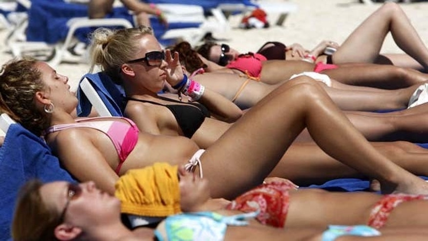 A group of spring breakers from Alberta, Canada, soak up the sun in Cancun, Mexico, Tuesday, March 14, 2006. The sugar-white sand beaches are back after being swept away by Hurricane Wilma five months ago. But there are no stages for wet T-shirt contests, and MTV won't be hosting its spring break beach party. Instead, the first wave of winter-weary college students who converged on Cancun found that construction workers nearly outnumbered revelers this week in Mexico's spring break capital of beer and bikinis.  (AP Photo/Gregory Bull)