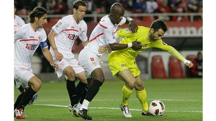 Villarreal's Giuseppe Rossi from Italy, right, and Sevilla's Didier Zokora from Ivory Coast, second right, fight for the ball as Sevilla's Fernando Navarro, second left, and Julien Escude from France, left, looks on during their La Liga soccer match at the Ramon Sanchez Pizjuan stadium on Sunday, April 24, 2011. (AP Photo/Angel Fernandez)