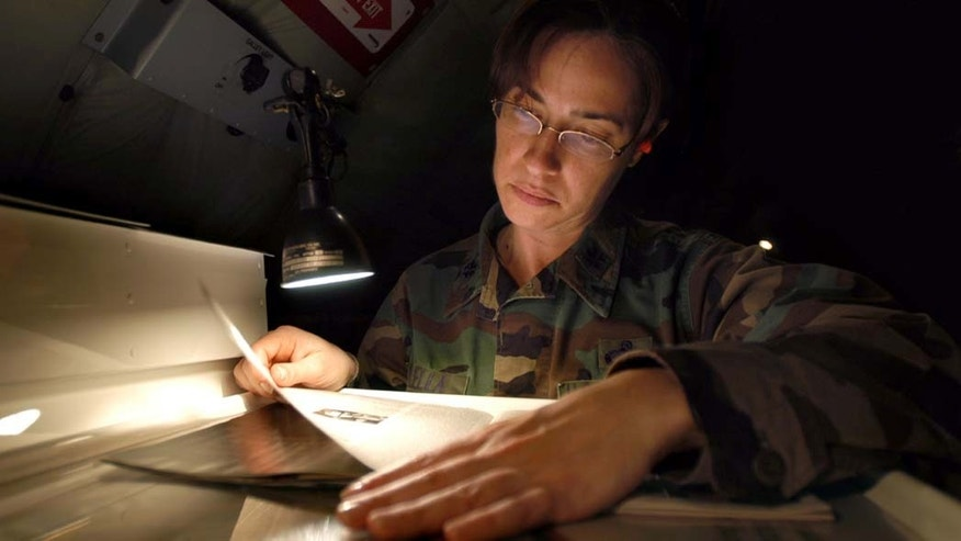 INCIRLIK AIR BASE, TURKEY--Lt. Col. Christina Vilella, 434th Aircraft Maintenance Squadron job title, catches up on some reading while trying to pass the time during an eleven-hour flight to Incirlik Air Base, Turkey. Colonel Vilella will assume the role of maintenance officer for the 385 Air Expeditionary Squadron during her deployment. (Air Force Photo/Senior Airman Mark Orders-Woempner)