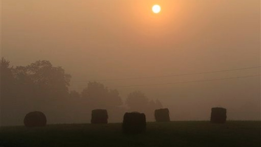 Round bales of hay lie in a field shrouded in fog as the sun rises Tuesday, July 12, 2011, near Glencoe, Ky. High heat and humidity continue to cover much of Kentucky.  The National Weather Service is calling for more hot weather Tuesday with heat index rising to 105 or higher and a heat advisory in effect for the afternoon in some areas.  (AP Photo/Ed Reinke)