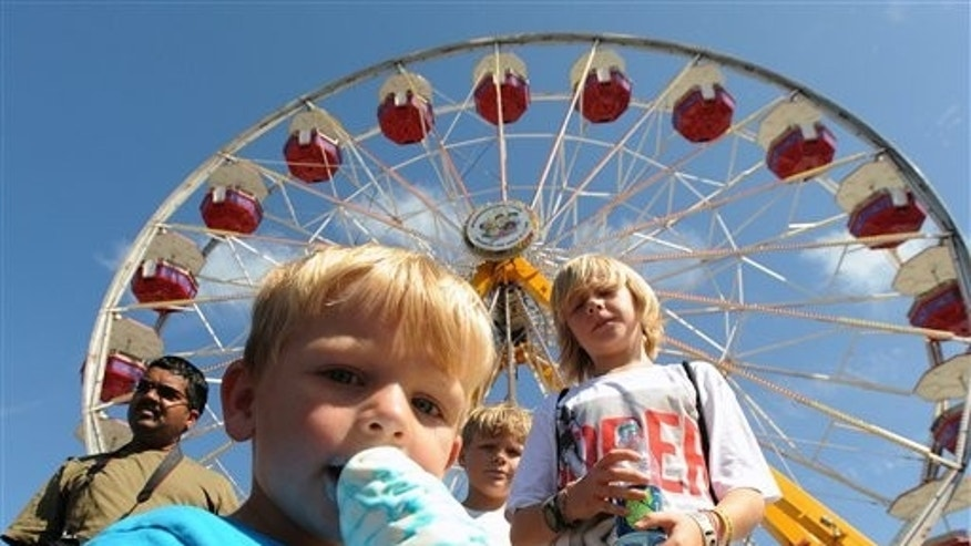In a July 30, 2011 photo, three-year-old Kye Waishes, of Houston tries to beat the heat melting his ice cream cone at the Delaware State Fair in Harrington, Del.  Saturday was the final day of the fair. (AP Photo/ The News Journal, Gary Emeigh) NO SALES