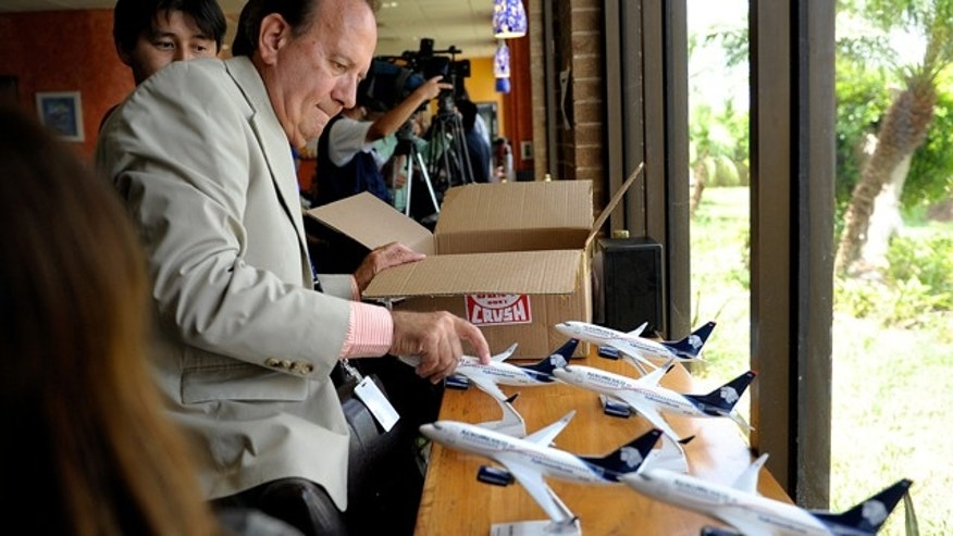 In this July 15, 2011 photo, Michael Jones, the business development manager at Brownsville South Padre Island International Airport in in Brownsville, Texas, lays out a series of model Aeromexico planes to be given to dignitaries upon the arrival of Aeromexico's first direct flight to the airport from Monterrey, Mexico.(AP Photo/The Brownsville Herald, Paul Chouy)