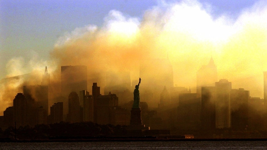 FILE - This Saturday morning, Sept. 15, 2001 file picture shows the Statue of Liberty from a vantage point in Jersey City, N.J., as the lower Manhattan skyline is shrouded in smoke following the Sept. 11 terrorist attacks on the World Trade Center in New York. (AP Photo/Dan Loh)