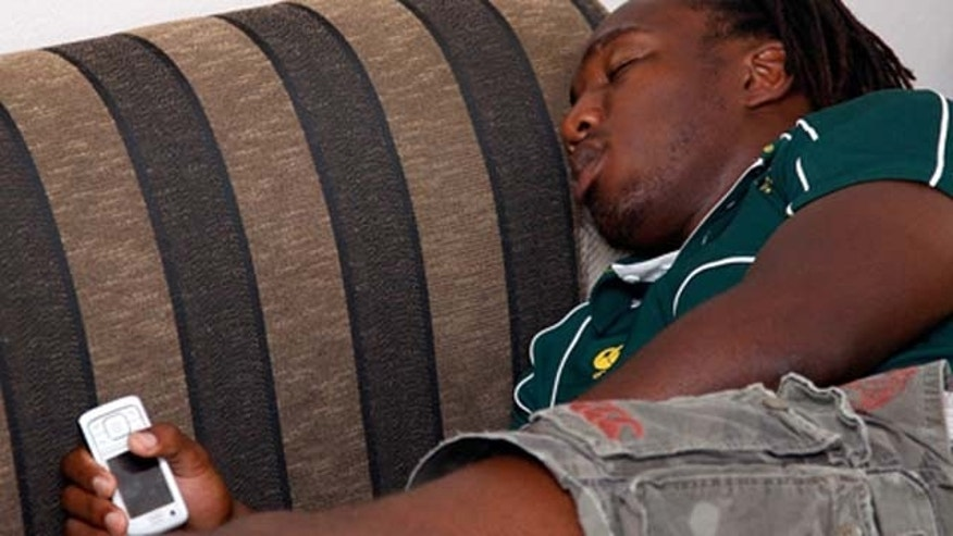 WELLINGTON, NEW ZEALAND - JANUARY 31: Jonathan Mokuena of the Springboks lays on the couch fast asleep still holding his cell phone before the jersey presentation at the James Cook Hotel January 31, 2008 in Wellington, New Zealand.  (Photo by Marty Melville/Getty Images)