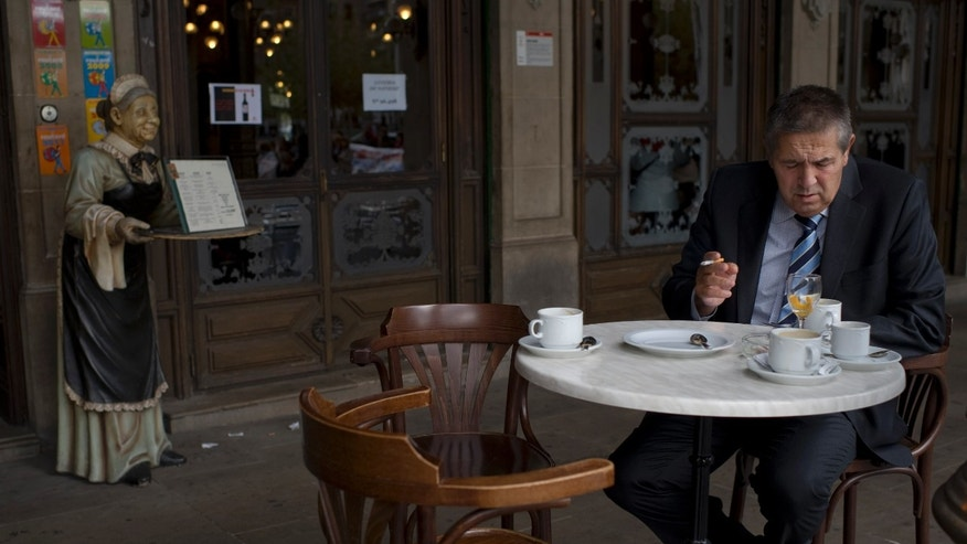 An executive sits with a coffee outside a restaurant in old city of Pamplona northern Spain. Amid sting of crisis, Spanish firms mull scrapping something sacred: the two-hour lunch break.