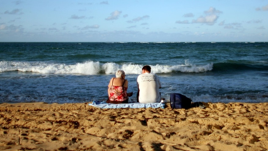 Two tourists sit in the sand on a beach in San Juan, Puerto Rico, Wednesday Nov. 23, 2011. The Caribbean anticipates another surge in visitors this winter, but officials warn that the amount the average tourist spends probably will decline. (AP Photo/Ricardo Arduengo)