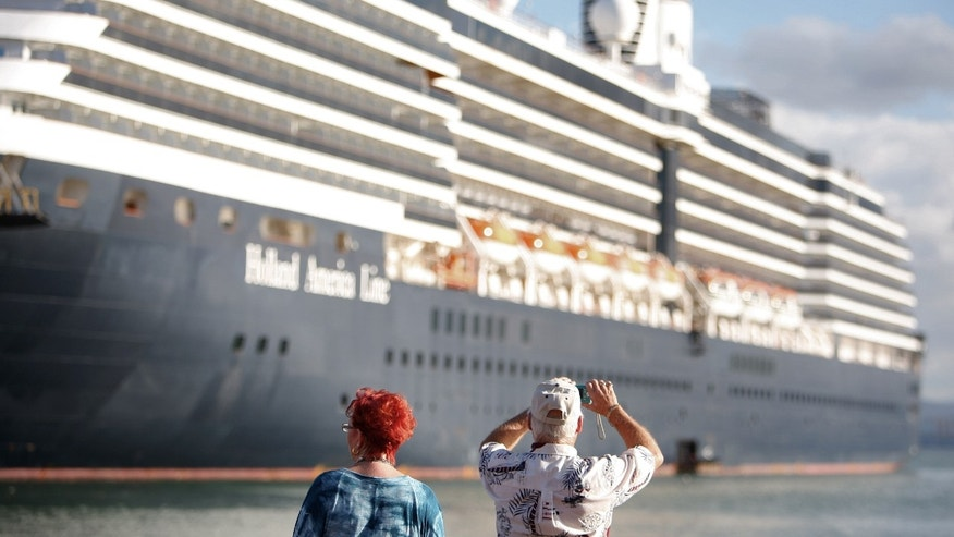 A tourist takes a photo of a cruise ship in Old San Juan, Puerto Rico, Wednesday Nov. 23, 2011. The Caribbean anticipates another surge in visitors this winter, but officials warn that the amount the average tourist spends probably will decline. (AP Photo/Ricardo Arduengo)