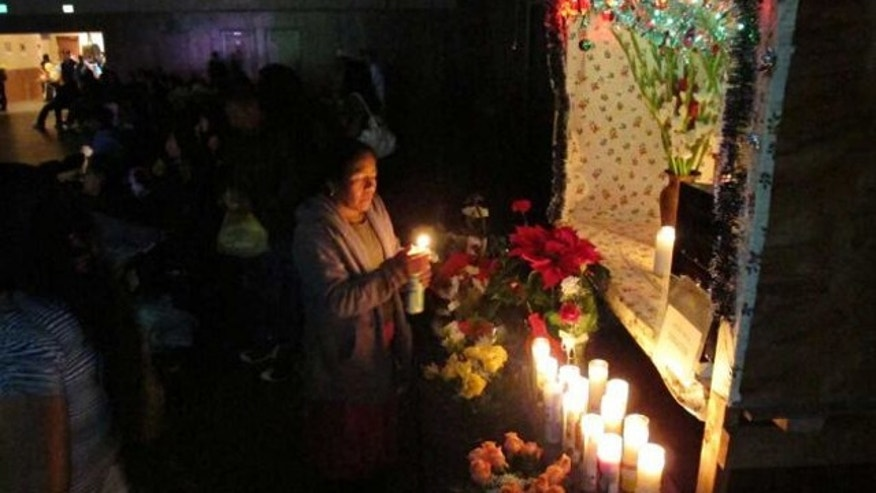 A Zapotec woman lights a candle at a mobile altar of Saint John the Evangelist in Madera, Calif. A fiesta held in the name of the patron saint of a village in the Mexican state of Oaxaca, is now celebrated by the indigenous migrant community in California.