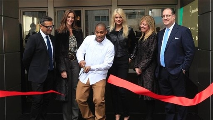 Victor Cruz, second from left, is joined by designer Naeem Kahn, left, Fashion at Lincoln Center director Stephanie Winston-Wolkoff, second from left, model Kate Upton, third from right, Mercedes-Benz Manager Lisa Holladay, second from right, and IMG Fashion Managing Director Peter Levy as he cuts the ribbon kicking off the Fall 2012 season at Mercedes-Benz Fashion Week,  Wednesday, Feb. 8, 2012 in New York.  (AP Photo/Mary Altaffer)