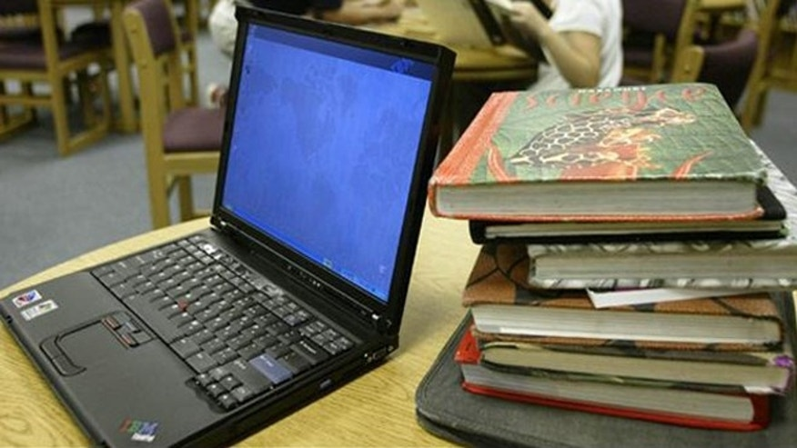 ** FILE ** An IBM ThinkPad computer, left, is shown next to a stack of text books that is issued to the typical fifth-grade at Johnson Elementary School, in Forney, Texas, in this , April 28, 2004, file photo. International Business Machines Corp. has reportedly put its personal computer business up for sale in a deal that could fetch as much as $2 billion and close an era for an industry pioneer that long ago shifted its focus to more lucrative segments of the computer business.  (AP Photo/stf/Donna McWilliam)