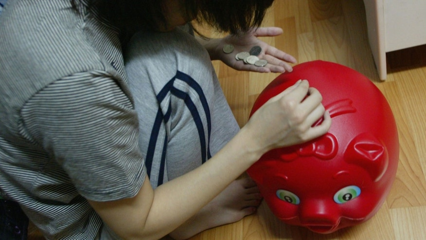 SEOUL, SOUTH KOREA - OCTOBER 19: A South Korean prostitute deposits her money into a piggy-bank in her room on October 19 2004, in Seoul, South Korea. The South Korean government began enforcing new laws last month to target human traffickers, pimps and prostitutes. The sex industry accounts for more than four percent of South Korea's gross domestic product (GDP), with its annual sales estimated at 24 trillion won (21 billion dollars) last year. Statistics show one in five South Korean men buy sex four times a month and 4.1 percent of women aged 20 to 30 rely on prostitution to make a living. (Photo by Chung Sung-Jun/Getty Images)