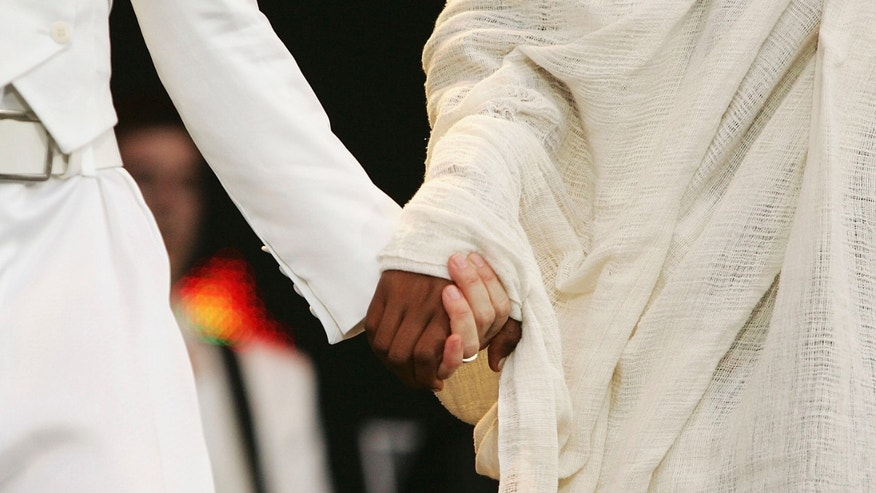 "LONDON - JULY 02:  Singer Madonna holds hands with 24-year-old student Birhan Woldu, former Ethiopian famine victim and the inspiration for Live Aid 1985, ""Live 8 London"" in Hyde Park on July 2, 2005 in London, England.  Twenty years ago, Woldu's face was featured in a video at Live Aid as a dying child with only 10 minutes to live before she was saved by aid workers.  (Photo by MJ Kim/Getty Images)"