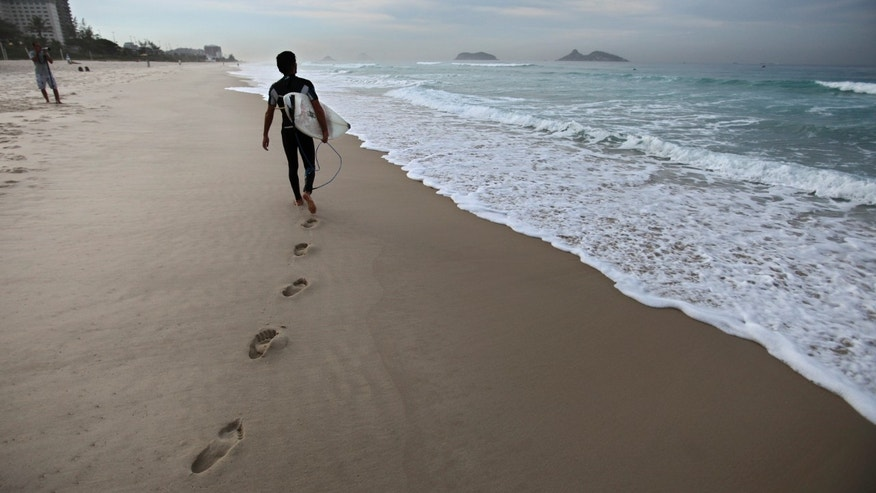 A surfer walks next to the shore at Barra da Tijuca beach before the start of the Billabong Rio Pro surfing championship in Rio de Janeiro, Brazil, Thursday, May 12, 2011. (AP Photo/Victor R. Caivano)