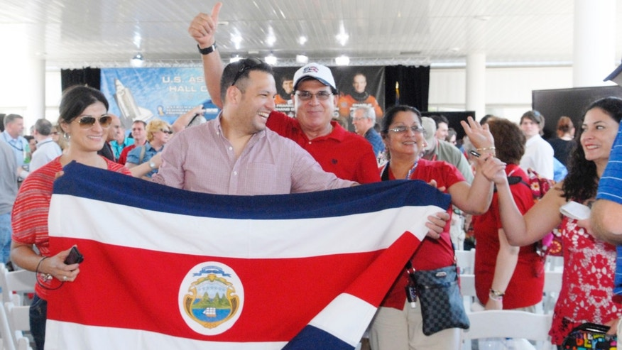 A family holds the flag of Costa Rica after Franklin Chang-Diaz was inducted into the Astronaut Hall of Fame, Saturday, May 5, 2012 at the Kennedy Space Center, Fla. Chang-Diaz, NASA's first Hispanic astronaut was among three astronauts  who joined John Glenn, Neil Armstrong and Sally Ride in the U.S. Astronaut Hall of Fame. (AP Photo/Florida Today, Tim Shortt)  NO SALES; MAGS OUT