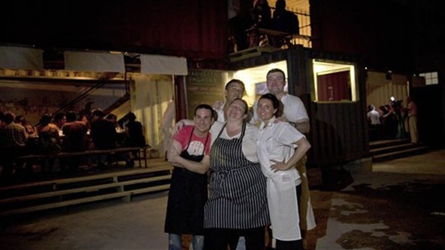 U.S. chef Sara Jenkins, center, and Cuban chef Hector Higuera, left, pose for a photo with their assistants in Havana, Cuba, Friday, May 11, 2012.