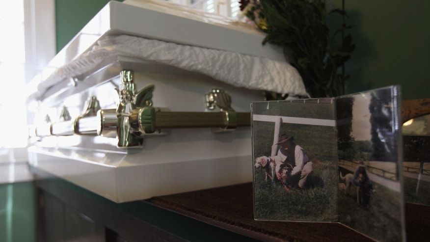 HARTSDALE, NY - APRIL 30: Photos of pet owner Spencer Warren and his dogs sit on display next to the coffin containing the body of his 12-year-old beagle-hound Justin in the viewing room of the Hartsdale Pet Cemetery and Crematory on April 30, 2012 in Hartsdale, New York. Warren, an Annandale, Virginia attorney, had traveled with Justin's body to bury him here on a shady hillside. The cemetery, established in 1896, is the oldest pet cemetery in the United States and serves as the final resting place for tens of thousands of pets. Pet owners can spend as much as $20,000 for a large plot to bury multiple pets and as little as $300-400 for small plots to bury ashes if they choose cremation. Pet owners also have the option of eventually having their own ashes buried in the plot, alongside their pets.  (Photo by John Moore/Getty Images)