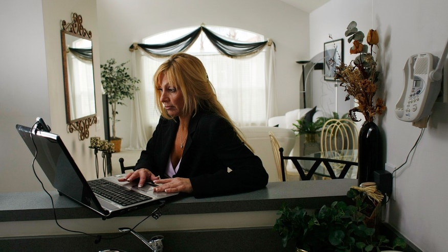 WEST PALM BEACH, FL - JULY 1:  Deven Trabosh checks her computer for emails in response to her Craigslist advertisement offering to sell her home along with the chance to marry her July 1, 2008 in West Palm Beach, Florida. Trabosh also tried eBay but the company removed the listing because they say they don't let people sell themselves on the website. Trabosh is a single mother of two girls and has been divorced for eight years and decided to combine the search for a husband and the sale of her house into one.  (Photo by Joe Raedle/Getty Images)