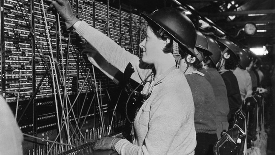 9th November 1940:  Women operators at a London telephone exchange wearing helmets during an air-raid alert.  (Photo by A. J. O'Brien/Fox Photos/Getty Images)