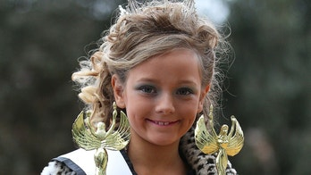 """MELBOURNE, AUSTRALIA - JULY 30:  A girl holds her two trophies that she won after competing in a child beauty pageant at Northcote Town Hall on July 30, 2011 in Melbourne, Australia. The controversial child beauty competition, kicked off today in Melbourne despite complaints and demonstrations by pageant opponents. Organised by the US-based pageant company that produces reality TV show """"Toddlers and Tiaras"""", Australian contestants will have the opportunity to pose with the reality show star, six year-old Eden Wood.  (Photo by Scott Barbour/Getty Images)"""