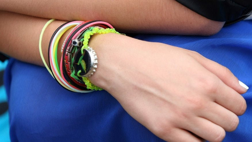 "BERLIN, GERMANY - JULY 21:  An attendee wears 1980s jelly bracelets at the second annual Hipster Olympics on July 21, 2012 in Berlin, Germany. With events such as the ""Horn-Rimmed Glasses Throw,"" ""Skinny Jeans Tug-O-War,"" ""Vinyl Record Spinning Contest"" and ""Cloth Tote Sack Race,"" the Hipster Olympics both mocks and celebrates the Hipster subculture, which some critics claim could never be accurately defined and others that it never existed in the first place. The imprecise nature of determining what makes one a member means that the symptomatic elements of adherants to the group vary in each country, but the archetype of the version in Berlin, one of the more popular locations for those following its lifestyle, along with London and Brooklyn, includes a penchant for canvas tote bags, the carbonated yerba mate drink Club Mate, analogue film cameras, an asymetrical haircut, 80s neon fashion, and, allegedly, a heavy dose of irony. To some in Berlin, members of the hipster ""movement"" have replaced a former unwanted identity in gentrifying neighborhoods, the Yuppie, for targets of criticism, as landlords raise rents in the areas to which they relocate, particularly the up-and-coming neighborhood of Neukoelln.  (Photo by Adam Berry/Getty Images)"