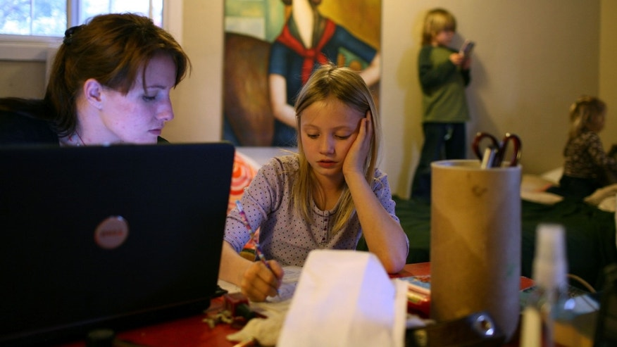 SACRAMENTO, CA - MARCH 05:  (L-R) Brittney Nance helps her daughter Izabella, 7, with homework as Henry Nance, 5, and Lillie Nance, 2, play on the bed in their motel room at the Old Town Inn March 5, 2009 in West Sacramento, California. Brittney and her family were evicted from the house they were renting after her husband, Steve Nance, lost his job. The couple and their three children are living  in a budget motel while they save enough money for deposit on a new rental home, but are finding it difficult as they pay nearly $1200 a month for the motel room. All five live in a small studio sized room with most of their belongings. (Photo by Justin Sullivan/Getty Images)