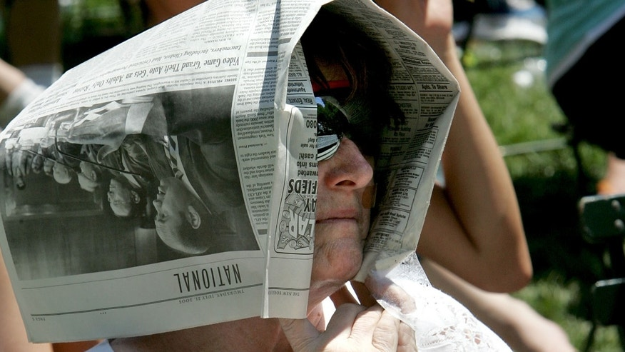 NEW YORK - JULY 21:  Sondra Fagen from Brooklyn Heights finds relief from the sun under her newspaper during 106.7 Lite FM presents Broadway in Bryant Park 2005, July 21, 2005 in New York City.  (Photo by Paul Hawthorne/Getty Images)
