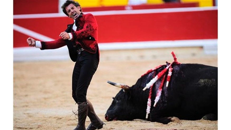 File - In this July 6, 2012 file photo, Spanish mounted bullfighter Pablo Hermoso de Mendoza celebrates beside a dead bull after a horseback bullfight in Pamplona, northern Spain.