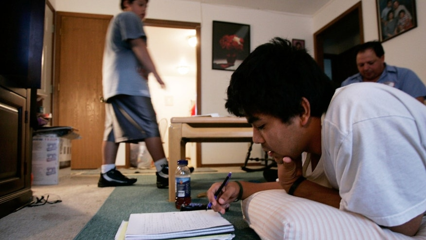 MARSHALL, MO - SEPTEMBER 28:  Francisco ?Paco? Inzunza's older son Paco Jr. (2nd R), a senior who has been taking honors classes at the Marshall High School, studies on the floor as his dad (R) and younger brother Anthony (L) are seen in the background at home September 28, 2005 in Marshall, Missouri. Paco illegally came to the United States to pursue his American dream from Mexico in 1991. After he and his family had settled in Marshall, he learned English for 3 years and started helping members of the local Latino community to translate for their daily lives. He was forced to admit his illegal statues when he was involved in a murder case as a translator and a witness. Paco is very well received by the people in his town because of his involvement in helping others. He also works very hard to support his own family. Many of his supporters had testified for him at his deportation hearing and tried to lobby for a law change before the next time he has to go back to court on February 13, 2007, so Paco can stay in the United States permanently.  (Photo by Alex Wong/Getty Images)