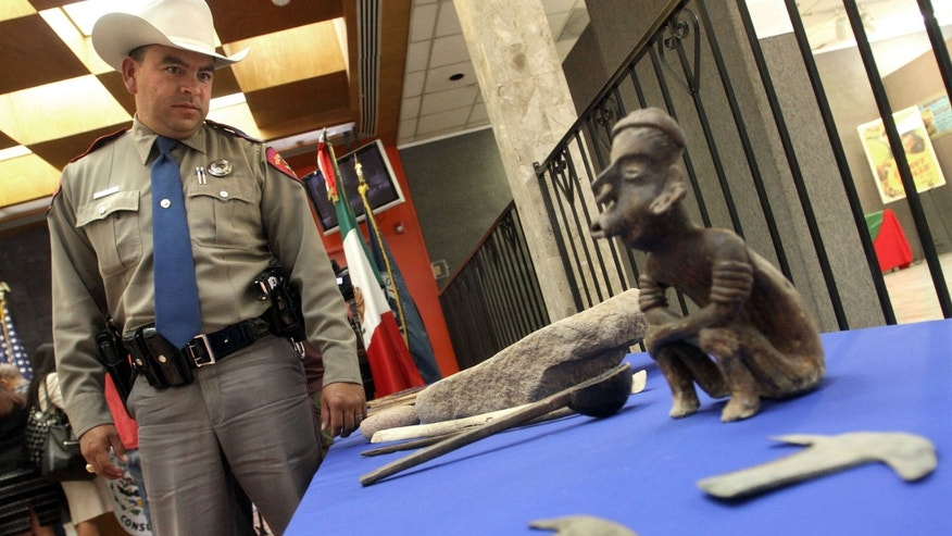 Trooper John Albert Barragan, left, who worked with Homeland Security Investigators, looks at a table with Mexican artifacts during a news conference at the Mexican Consulate in El Paso, Texas, Thursday, Oct. 25, 2012.