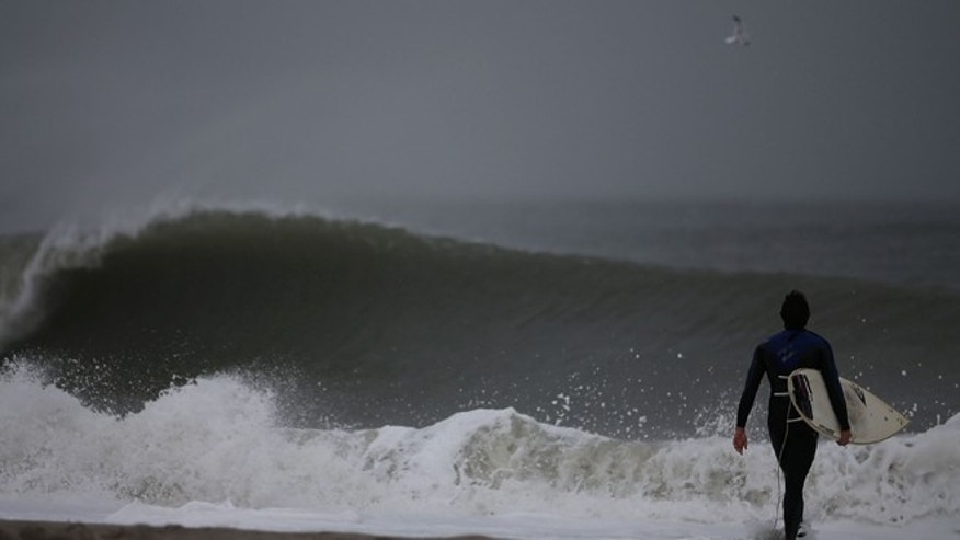 CAPE MAY, NJ - OCTOBER 28: A surfer walks into the heavy surf caused by approaching hurricane Sandy, on October 28, 2012 in Cape May, New Jersey. Hurricane Sandy is expected to hit the New Jersey coastline sometime on Monday bringing heavy winds and floodwaters.  (Photo by Mark Wilson/Getty Images)