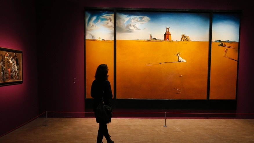 "In this photo taken Monday Nov. 19, 2012, a women looks at a painting by Spanish artist Salvador Dali (1904-1989) during the presentation to the press of the exhibition ""Dali"" at the Centre Pompidou modern art museum, in Paris."