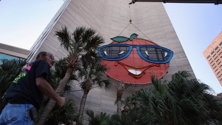 Bill Flaherty from Mr. Neon inc. helps place the Big Orange New Year's time ball onto the side of the Hotel Intercontinental in Miami, Florida.