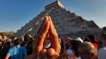 A man holds a crystal above his head as he and over 15,000 people congregate in front of the famous pyramid at Chichen-Itza, Mexico to celebrate the arrival of the Equinox signaling the beginning of Spring, Sunday, March 20, 2011.  The famous Mayan ruin is popular at the Equinox when the serpent's back shows on the side of the stairway that leads to the top. (AP Photo/Standard Times , Peter Pereira)