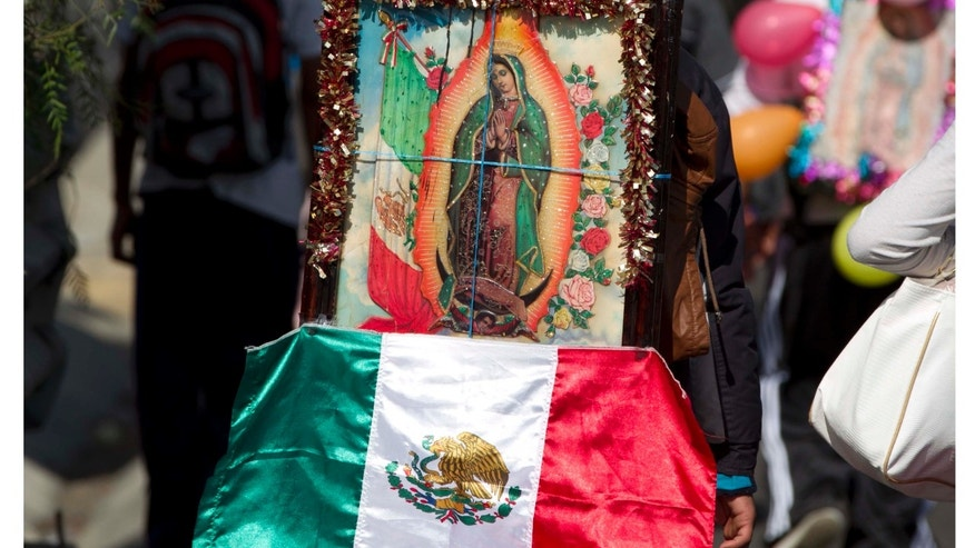 A pilgrim carries a statue of the Virgin of Guadalupe on his back as he makes his way with other pilgrims toward the Basilica of Guadalupe along a highway entering Mexico City, Tuesday, Dec. 11. 2012.  Nationwide, devotees of the Virgin of Guadalupe make a pilgrimage to the basilica with images of her to be blessed in honor of her Dec. 12 feast day. (AP Photo/Eduardo Verdugo)