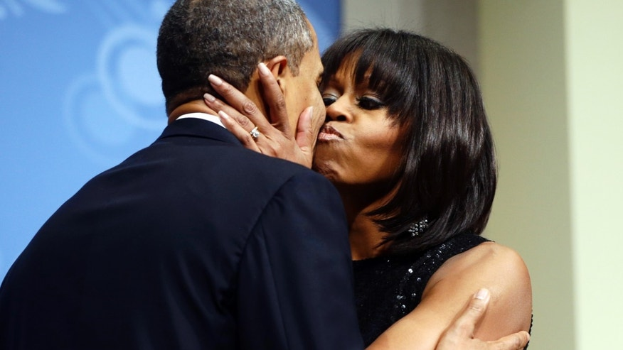 President Barack Obama kisses first lady Michelle Obama at an inaugural reception for the 57th Presidential Inauguration at The National Building Museum in Washington, Sunday, Jan. 20, 2013.