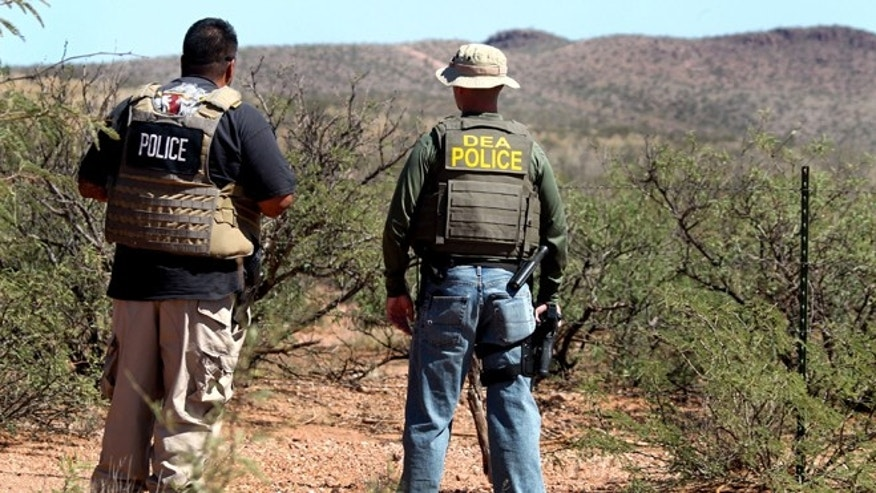 Det. Bill Silva, left, with the Bisbee Police Department, and an unnamed agent with the Drug Enforcement Administration patrol a fence line east of Naco, Ariz., after a Border Patrol agent was killed early Tuesday, Oct. 2, 2012. The shooting occurred after an alarm was triggered on one of the thousands of sensors placed by the U.S. government along the border, and the agents went to investigate, said Cochise County Sheriff's spokeswoman Carol Capas. (AP Photo/Arizona Daily Star, Mike Christy)  NO MAGS NO SALES, MANDATORY CREDIT