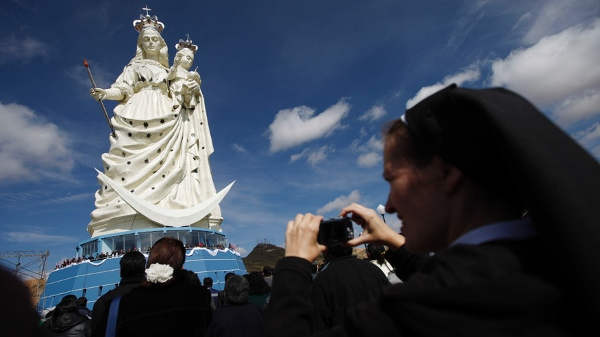 "A nun takes pictures of a newly unveiled statue of the Virgin Mary holding a baby Jesus on Santa Barbara hill in the mining city of Oruro, Bolivia. The 45 meter (147 feet) statue that took four years to build, known in Spanish as ""Virgen del Socavón,"" or the Virgin of the Tunnel, is Oruro's patron, venerated in particular by miners and folkloric Carnival dancers. (AP Photo/Juan Karita)"